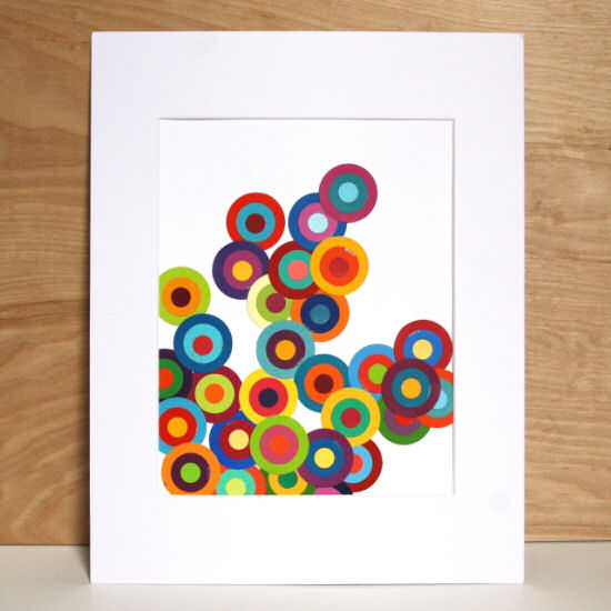 Create bold modern art by cutting circles in varying sizes from paint chips, and layering them.  From The 3 R's blog.