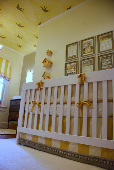 Yellow and white nursery with yellow ceiling with clouds and birds