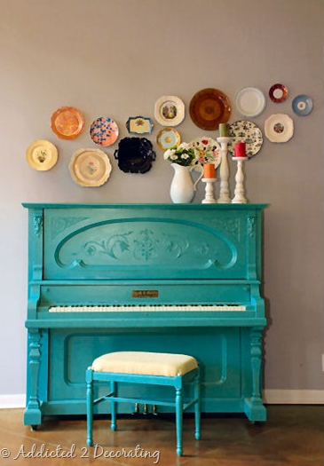 free form colorful plate wall over turquoise piano
