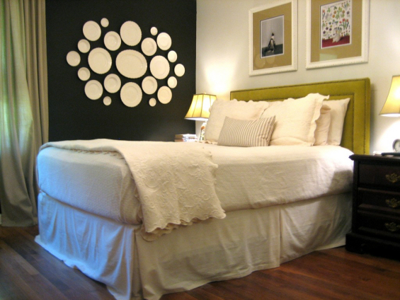 graphic decorative plate wall in bedroom--white plates on black wall