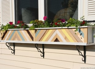 Plain white window planter box dressed up with painted scrap wood pieces in a chevron design