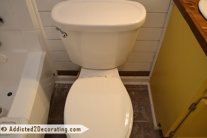 Bathroom makeover day 15 - trim behind toilet and around the tub