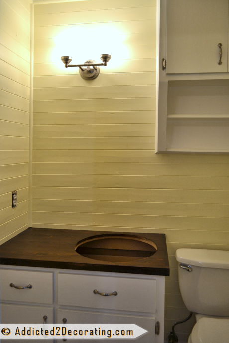 Tiny bathroom makeover with pale yellow walls and white cabinets