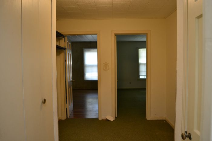 Hallway with original hardwood floors hidden under green carpet