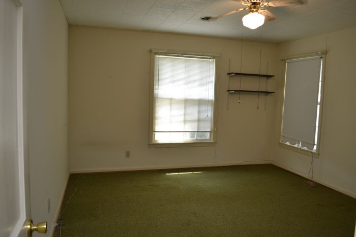 Master bedroom with original hardwood floors hidden under green carpet