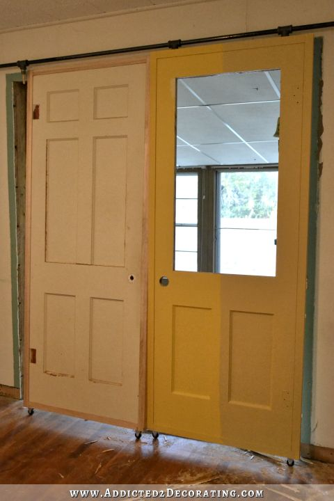 DIY rolling door painted in two shades of yellow from Behr - jackfruit on the left and warm muffin on the right