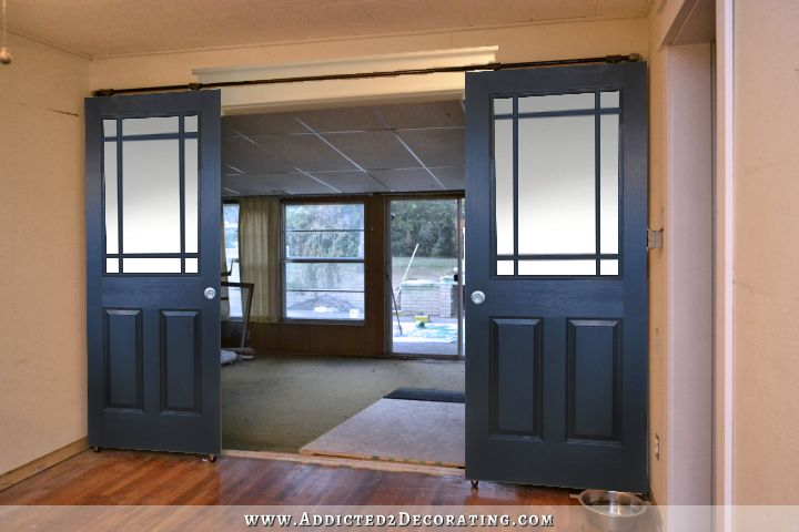 Black rolling barn door style doors with six panes of glass of unequal size on top