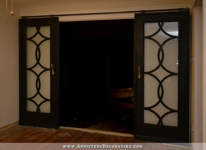 DIY French doors with circle fretwork panels, installed on rolling barn door-style hardware
