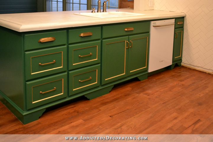 kitchen peninsula with green cabinets with gold leaf details and white concrete countertops