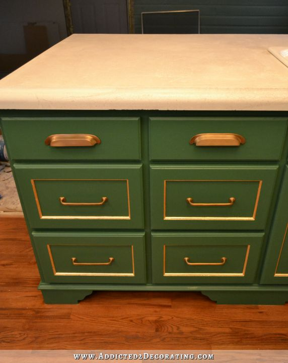 kitchen peninsula cabinets painted green with gold leaf accents and antique brass hardware, with white concrete countertop
