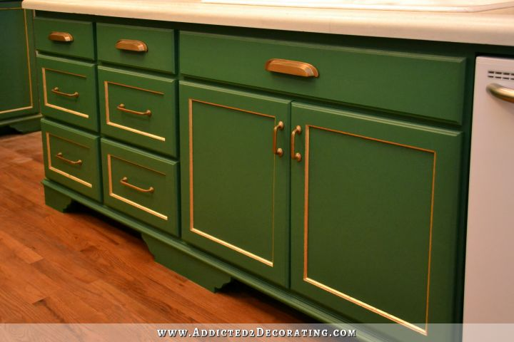 Green kitchen cabinets with gold leaf accents and antique brass hardware, with white concrete countertops