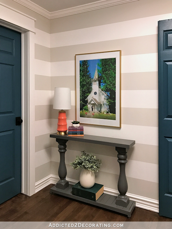 hallway after remodel - striped walls, teal doors, gray console table, watercolor artwork