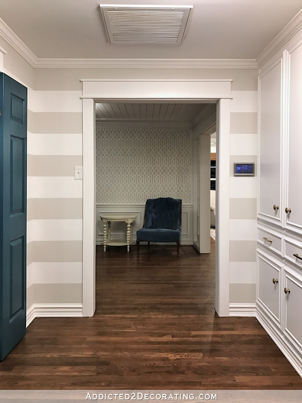 hallway after remodel - widened doorway, teal doors, custom linen cabinet, striped walls