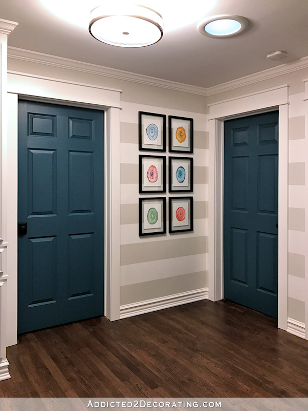 hallway after remodel - teal doors, striped walls, watercolor geode prints