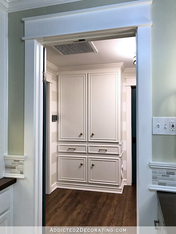 hallway after remodel - custom linen cabinet with compartment for hidden cat litter box, view from hallway bathroom