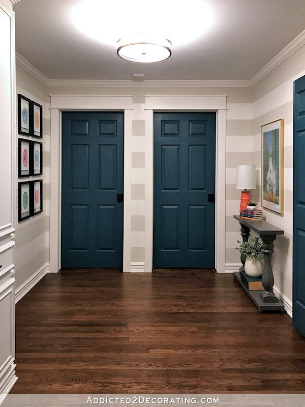 hallway after remodel - original hardwood floors, teal doors, striped walls, watercolor artwork