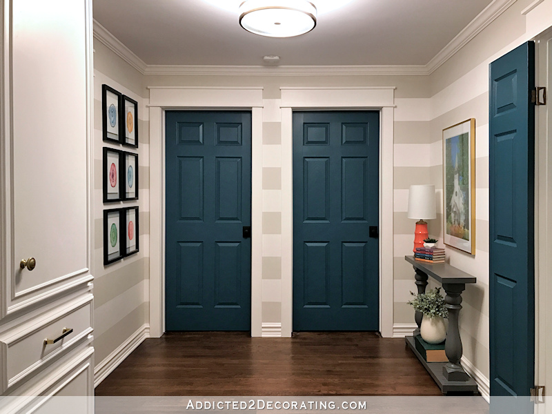 hallway after remodel - teal doors, striped walls, watercolor artwork
