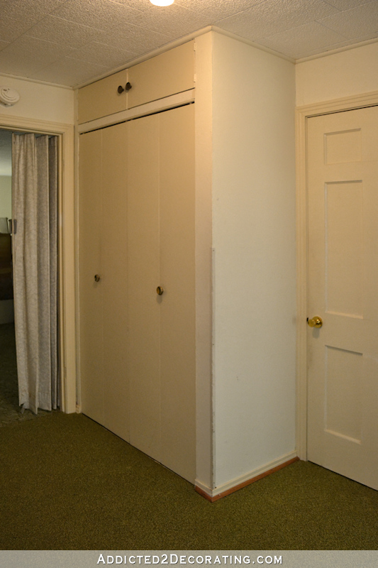 hallway before remodel - 1970s closet, narrow cased opening, green carpet