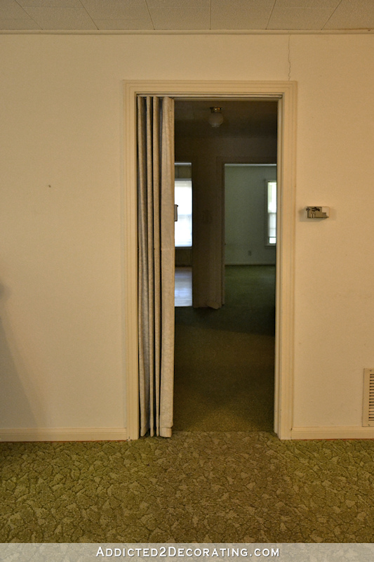 hallway before remodel - narrow cased opening into hallway, green carpet