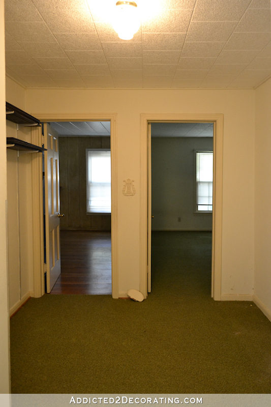hallway before remodel - green carpet, shelves