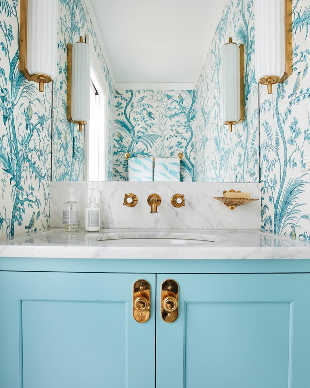 Bathroom with turquoise and white wallpaper, turquoise vanity, brass and white lights, from Amie Corley Interiors (@amiecorleyinteriors) on Instagram