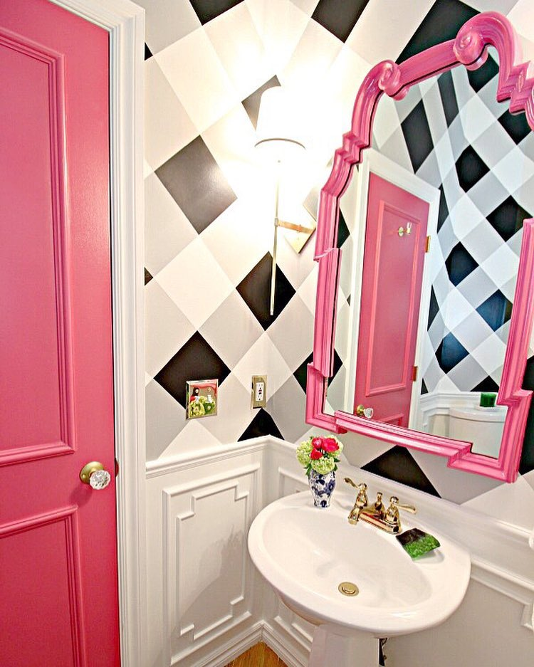 Small bathroom with black and white checked walls, bold pink door and mirror frame, white wainscoting, from Jennifer at Dimples and Tangles (@jenniferdimplesandtangles) in Instagram